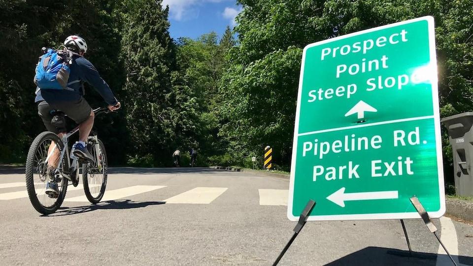 Une cycliste s'engage sur la chaussée du parc Stanley.