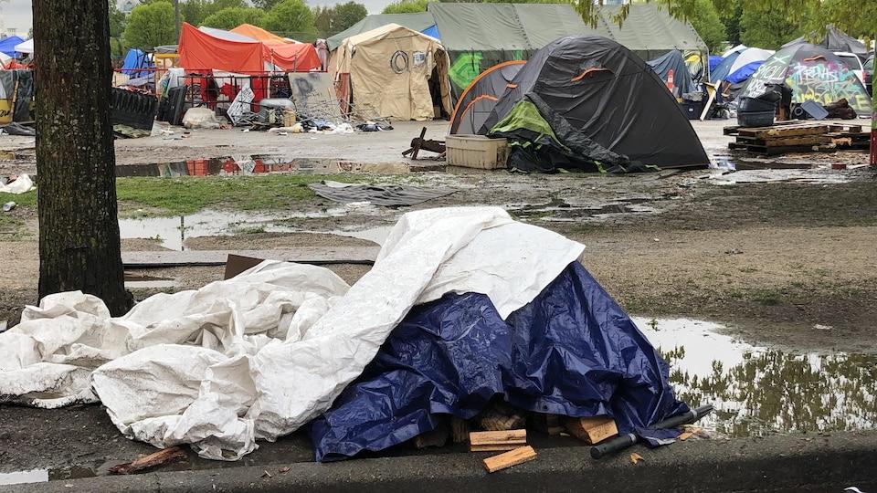 Au premier plan, des bâches en plastique jonchent le sol alors qu'en arrière-plan, plusieurs tentes sont encore debout.