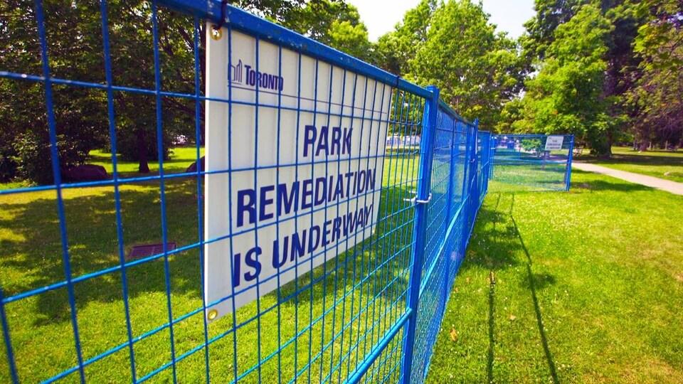 La clôture en métal bleue bloquant l'accès à une partie du parc.
