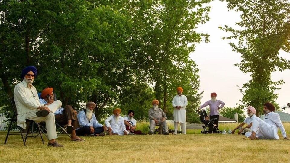 Des personnes sur un espace vert dont certains sont assises sur des chaises et d'autres à même le sol.