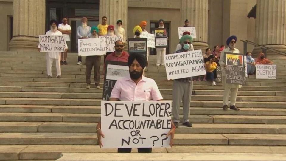 Des personnes tiennent des pancartes sur lesquelles il y a des inscriptions et sont debout sur des marches d'escaliers.