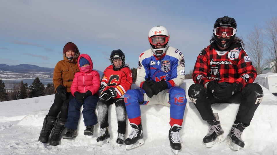 Deux adultes et un garçon en tenue de patinage extrême sont assis sur un banc de neige. Une femme et une fillette en habit d'hiver se trouvent à leur côté.
