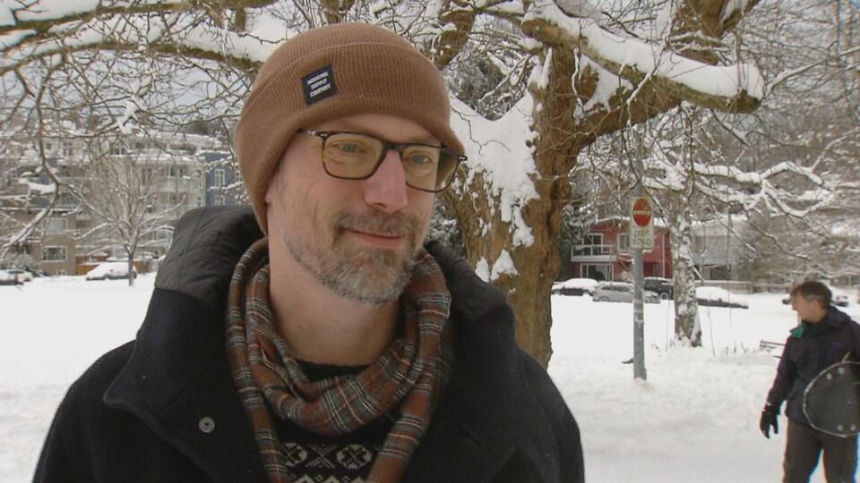 Plan moyen de Thibault Mayor debout dans un parc enneigé.