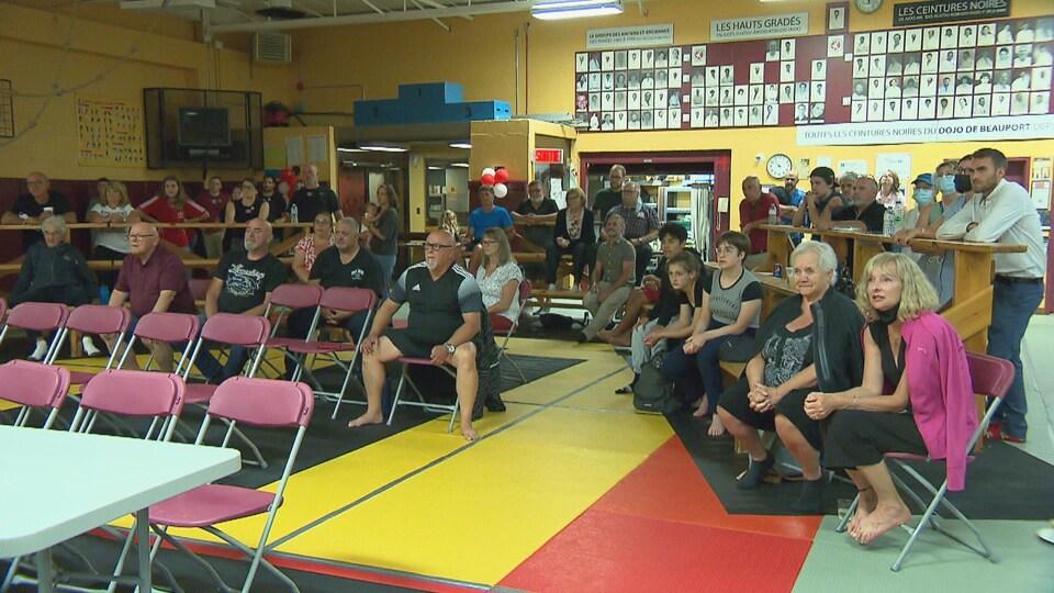 Plusieurs personnes assises et debout regardent en direction d'un écran.