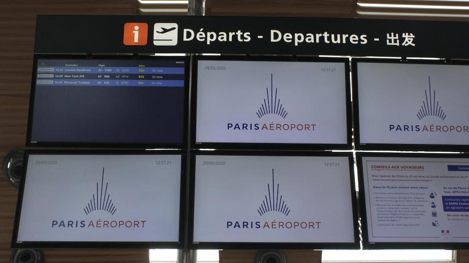 Un écran où sont écrits les vols de départs dans un aéroport.