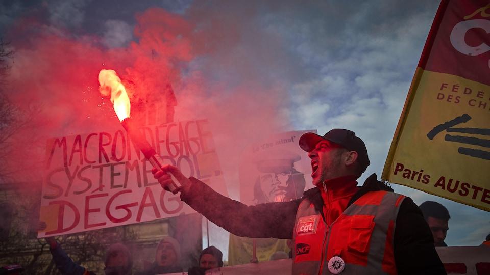 Un homme tient une fusée d'urgence allumée, des gens tiennent des affiches derrière lui.