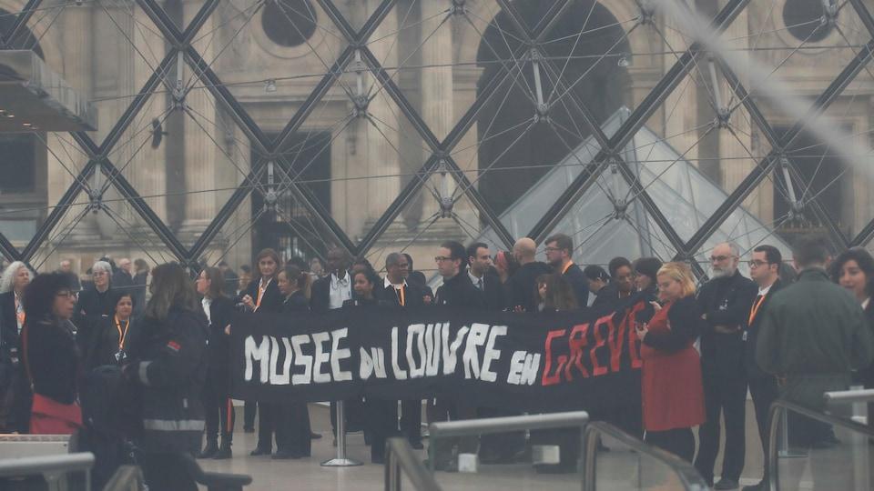 Un groupe de personnes devant le Louvre, à Paris, avec une bannière où il est écrit « Musée du Louvre en grève ».