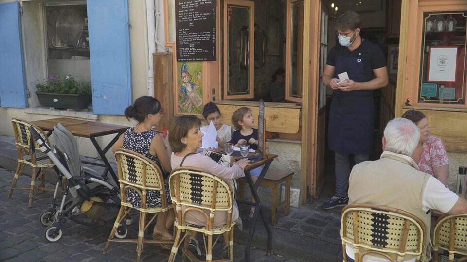 Un restaurateur portant un masque de protection discute avec des clients attablés à l'extérieur de l'établissement.