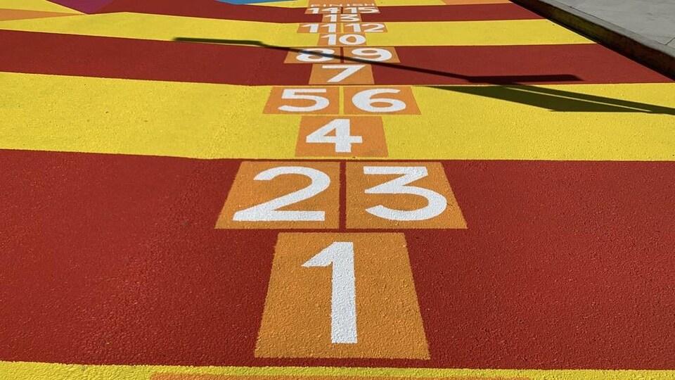 Un jeu de marelle peint en orange sur la rue.