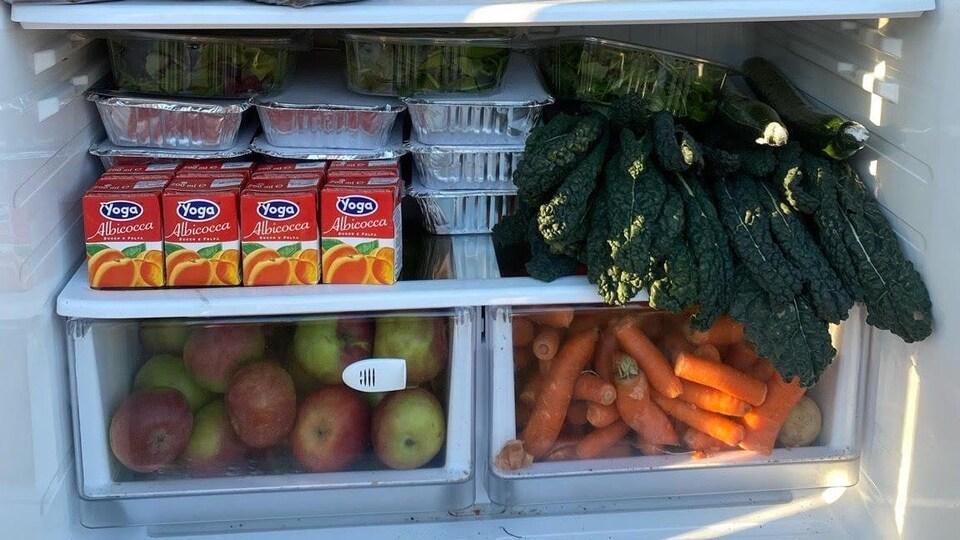 Des légumes, fruits et boîtes de jus dans un réfrigérateur.
