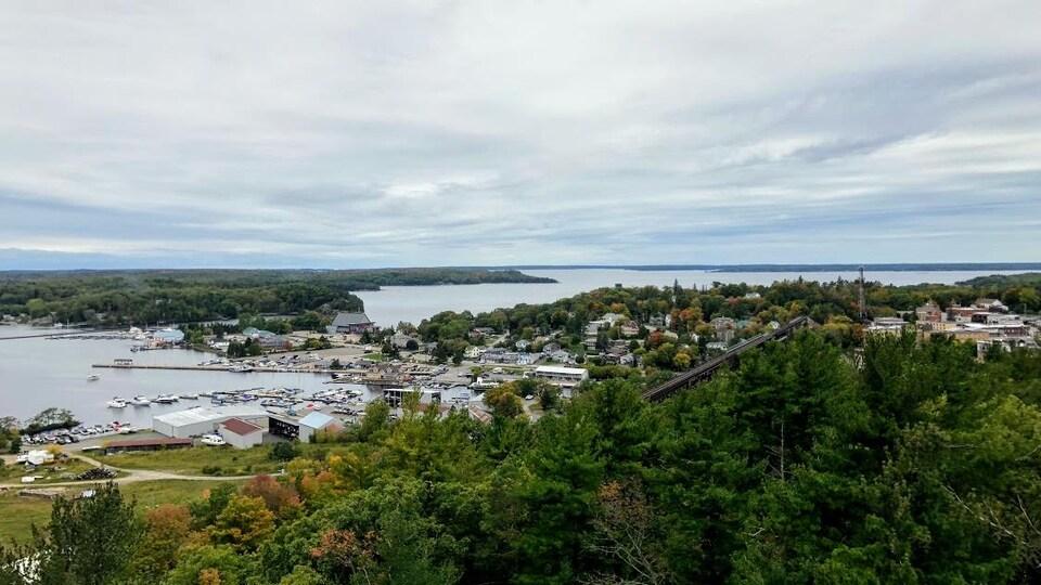 Une ville près d'un lac, vue en plongée. On distingue une marina, des bâtiments et un pont ferroviaire.