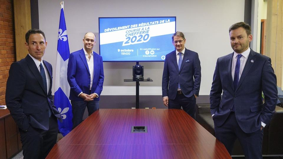 Frédéric Bastien, Guy Nantel, Sylvain Gaudreault et Paul St-Pierre Plamondon posent autour d'une table de conférence.