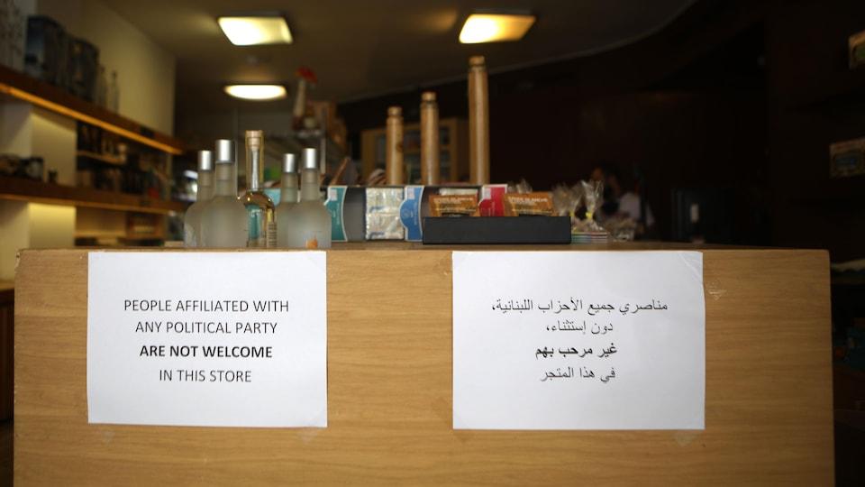 Deux pancartes, l'une en arabe et l'autre en anglais, accrochées sur un comptoir.