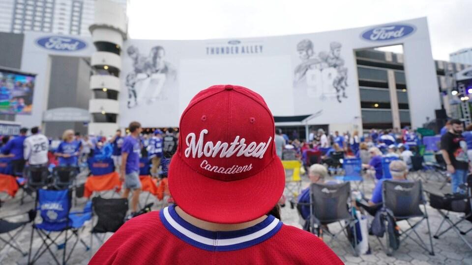 Un partisan portant une casquette du Canadien devant de nombreuses personnes aux couleurs du Lightning, près du Amalie Arena.