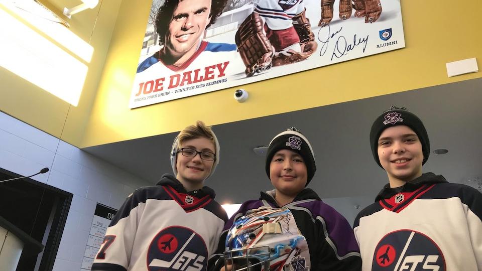 Trois jeunes joueurs de hockey, Shaw, Alexander et Jake, devant la murale de Joe Daley.