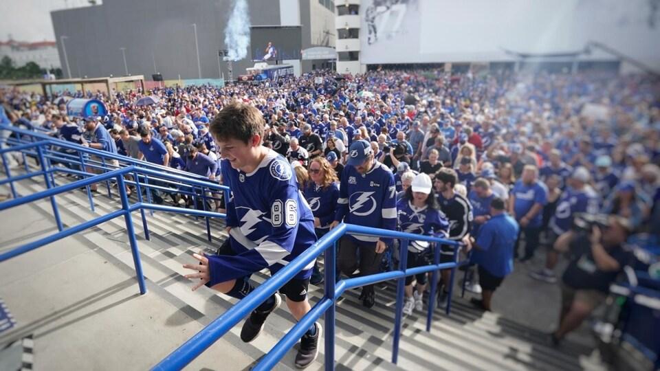 Un garçon portant un chandail du Lightning court pour entrer dans l'Amalie Arena, tandis qu'on voit une foule de partisans derrière lui.