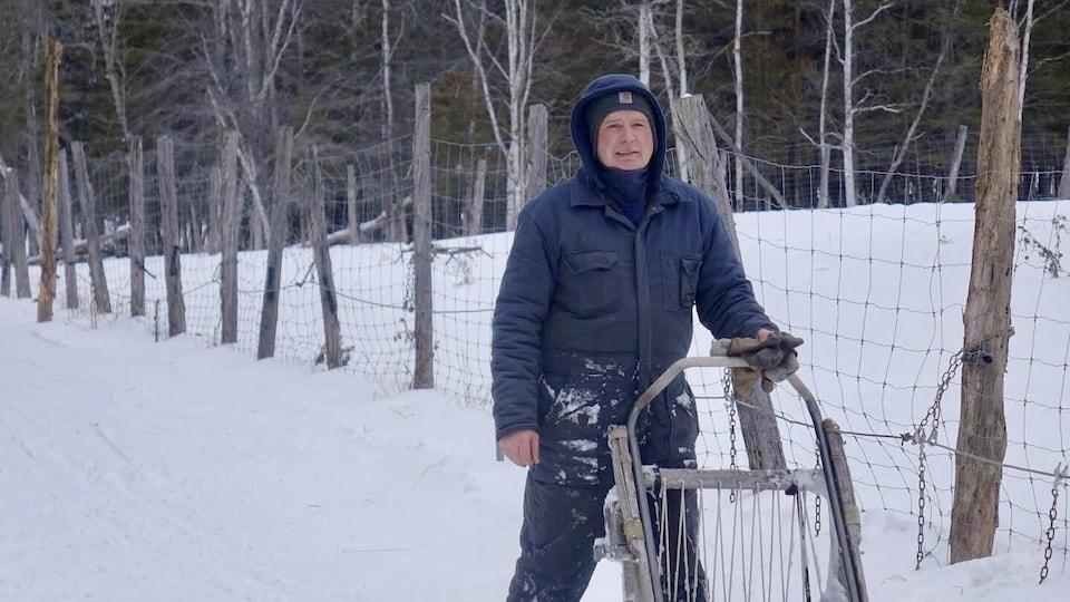 Un homme est en habit d'hiver et tient de la main droite un traîneau pour une randonnée avec des chiens.
