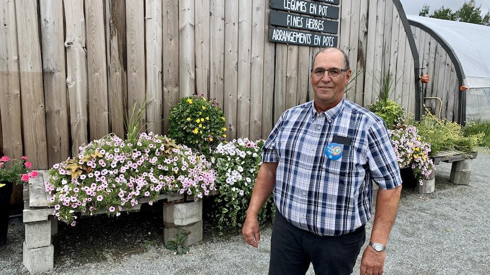 Pascal Rheault devant des fleurs.