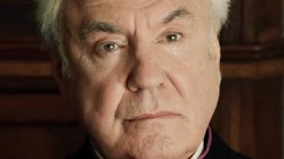 Un homme en tenue ecclésiastique.
