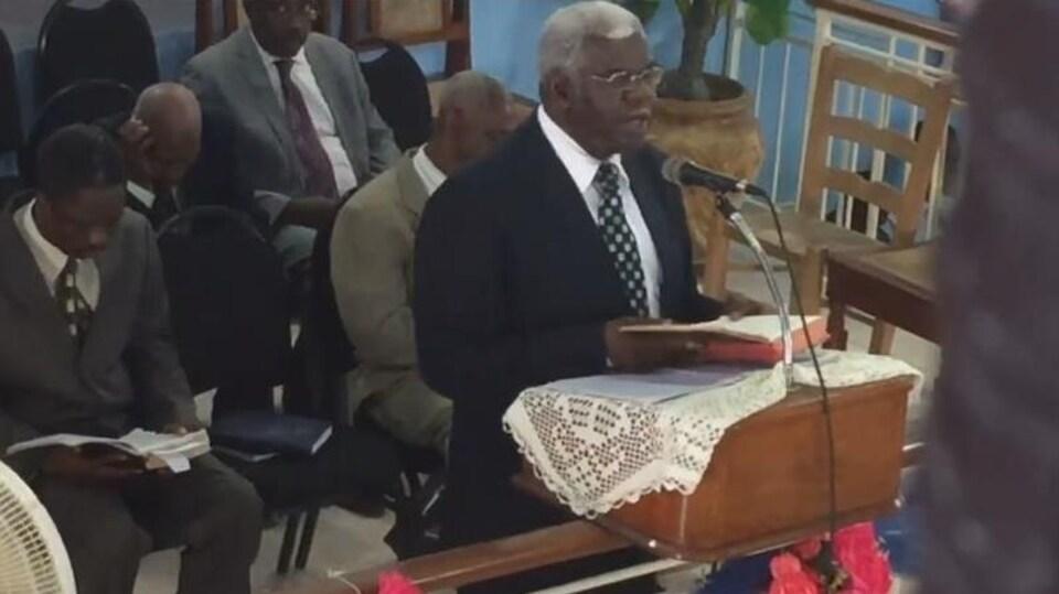 On voit, en plongée, le pasteur haïtiens parler debout devant les fidèles réunis dans l'église. Derrière lui, des hommes sont assis et écoutent ses paroles en lisant les écritures.