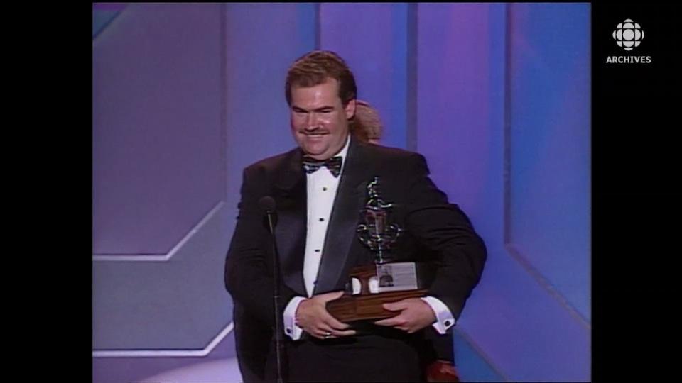 Pat Burns souriant tient son trophée.