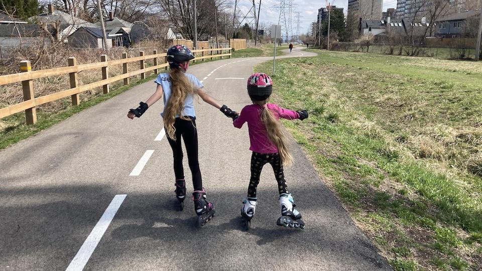Deux filles en patins à roues alignées.