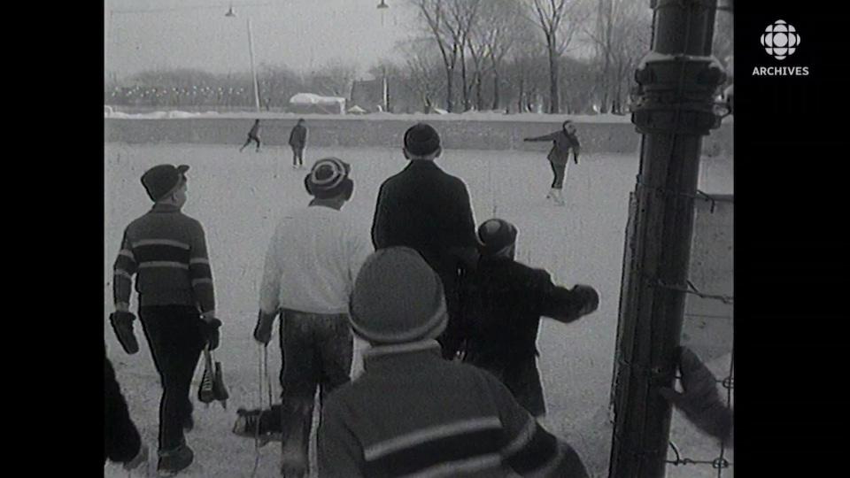 Jeunes vus de dos qui marchent vers la patinoire en tenant leurs patins dans leurs mains.