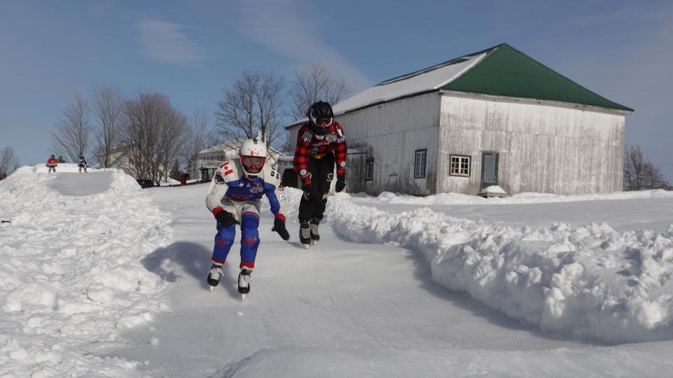 Deux patineurs descendent un parcours extrême aménagé sur une terre agricole.