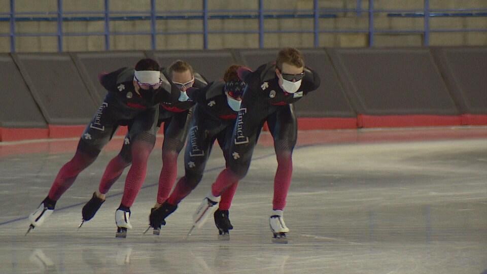 Des patineurs de vitesse s'entraînent en portant un masque.