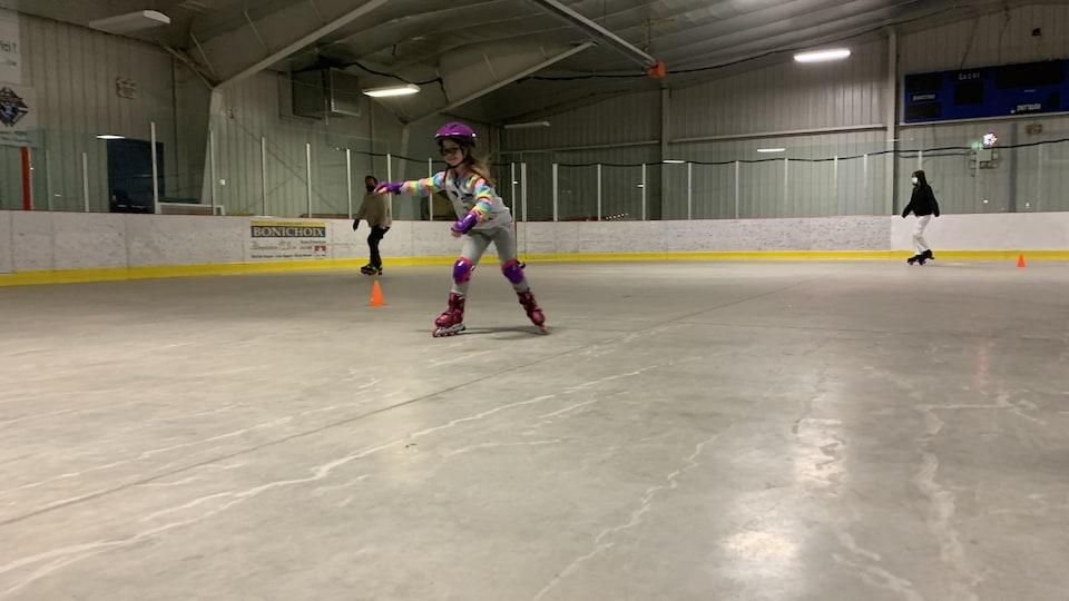 Une fillette essaie du patin à roues alignées.