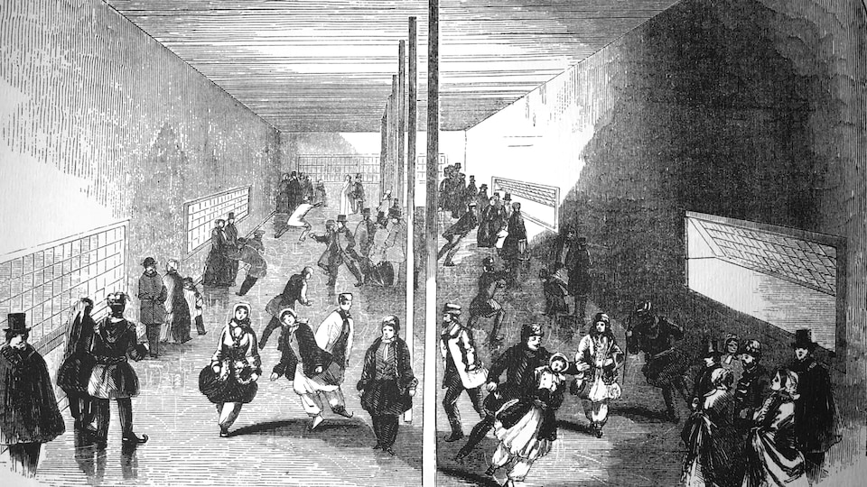 Des patineurs des deux sexes chaudement vêtus s'activent sur une patinoire intérieure soutenue par une rangée de piliers, au centre, et bordée par de larges fenêtres qui laissent entrer l'air froid.