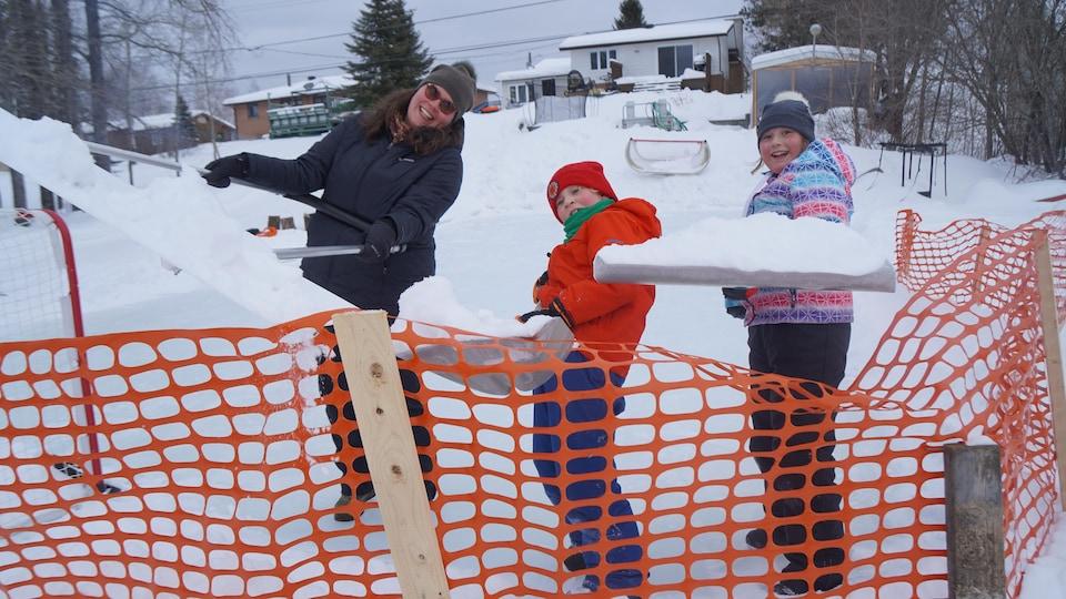 Une maman et ses enfants déneigent une patinoire.