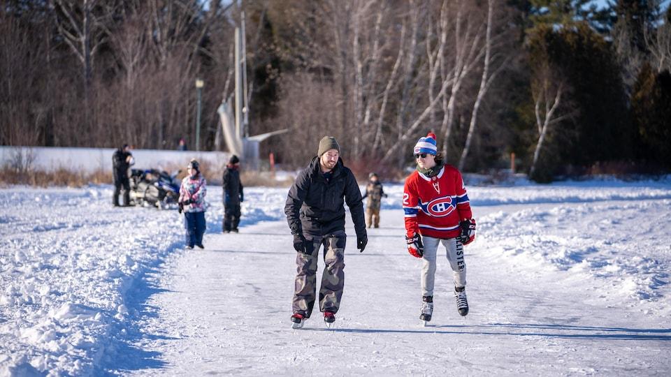 Deux patineurs, dont un arborant un jersey du Canadien, patinent sur un lac.