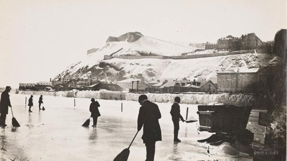 Des gens armés de balais et de pelles sont occupé à dégager un large espace pour patiner sur le pont de glace qui s'est formé entre Québec et Lévis.