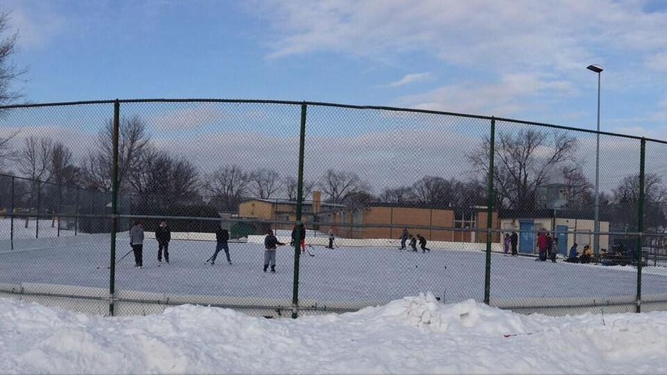 Des jeunes jouent au hockey sur la glace.