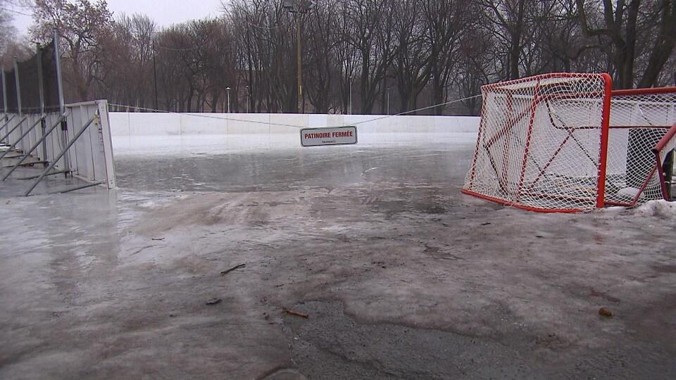 Une affiche indique qu'une patinoire est fermée. La glace semble mouillée et fondue.