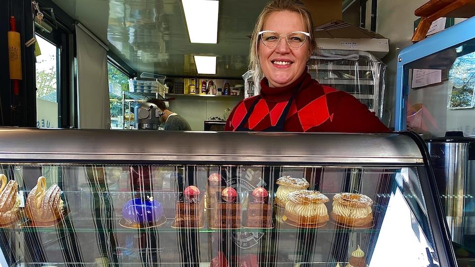 Jessyca Nason, copropriétaire de Ouest Artisan Pâtisserie devant un comptoir de pâtisseries.
