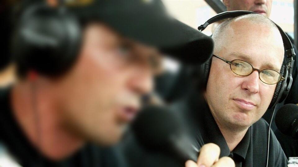 Patrice Demers avec de petites lunettes rondes et un polo noir. Il porte un casque d'écoute.