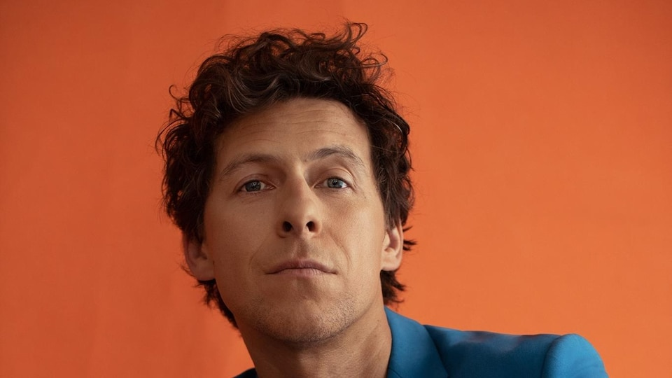 Un homme dans un veston bleu sur fond orange.