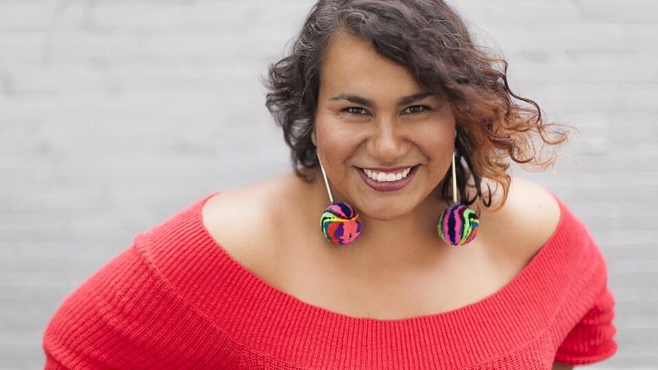 Une femme habillée en rouge avec des boucles d'oreilles multicolores et des cheveux bruns ondulés.