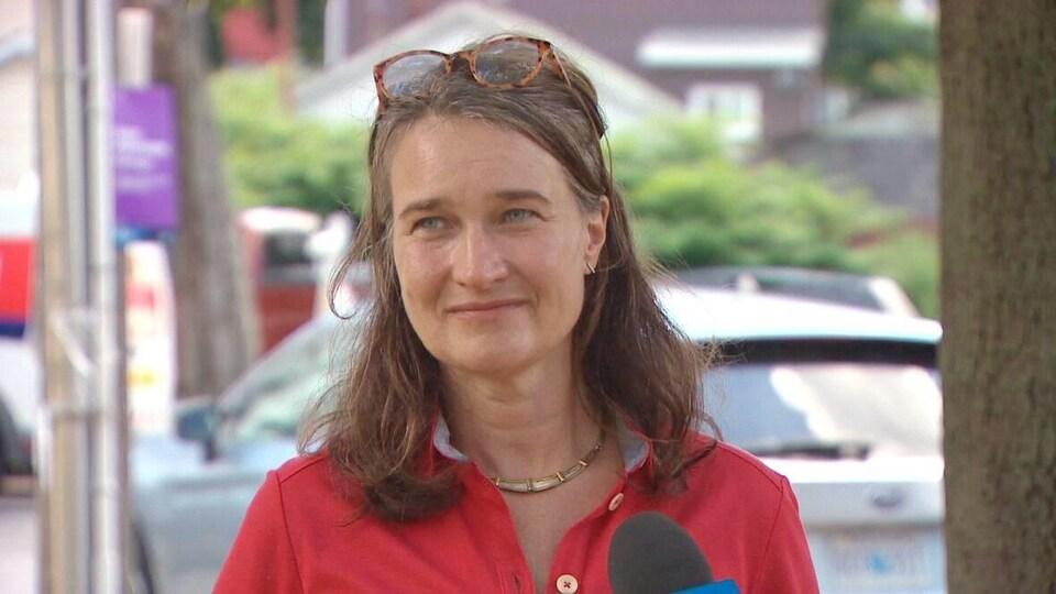 Patty Cuttell en entrevue sur un trottoir, en été.