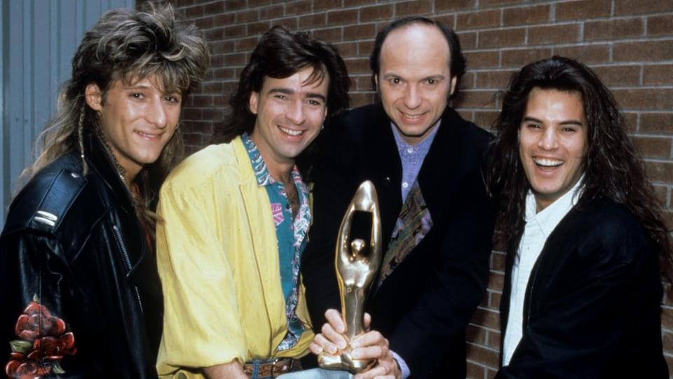 Les membres du groupe Les BB, François Jean, Alain Lapointe et Patrick Bourgeois, en compagnie de l'animateur du Gala de l'Adisq, Michel Rivard, tenant un trophée Félix dans ses mains. C'était en 1990.