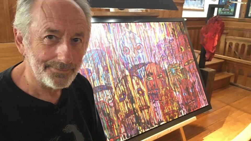 Patrick Cady, copropriétaire du Musée d'art contemporain singulier de Mansonville, pose près d'une toile.