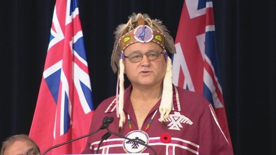 Un chef autochtone portant la coiffe traditionnelle se trouve derrière un lutrin.