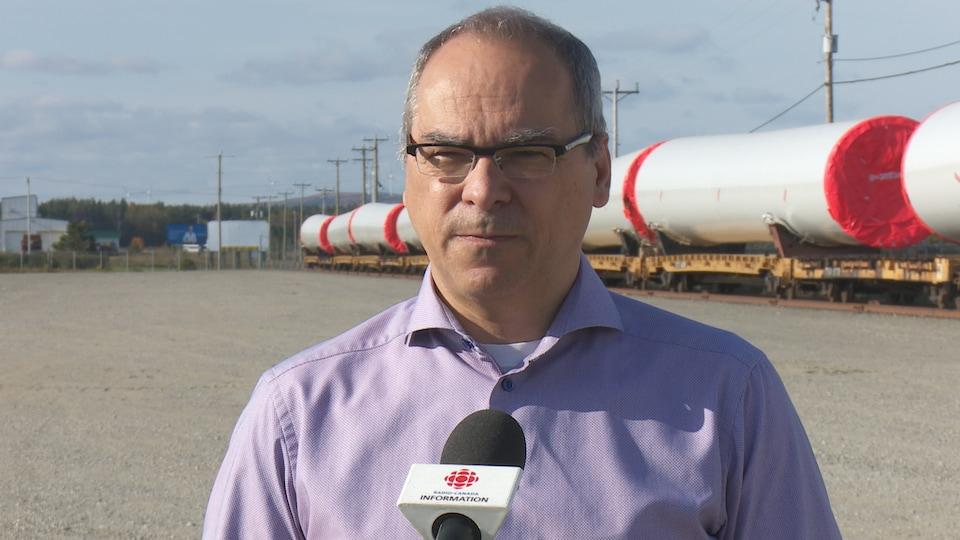 Patrick Pellerin devant des morceaux d'éoliennes.