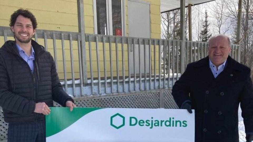 Deux hommes tiennent une pancarte de Desjardins devant le chalet.