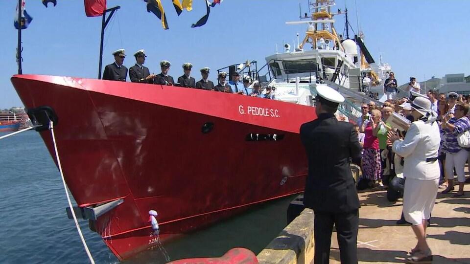 Une foule sur un quai applaudit les marins sur le navire