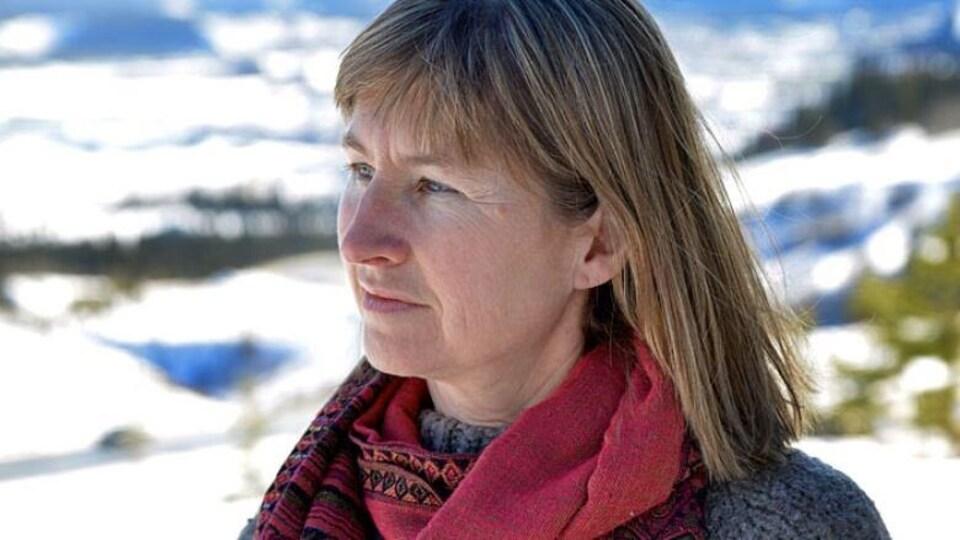 Patti Flather est à l'extérieur l'hiver et esquisse un sourire en regardant au loin.