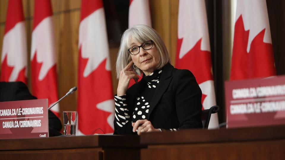 La ministre écoute une question lors d'une conférence de presse, assise devant des drapeaux canadiens.