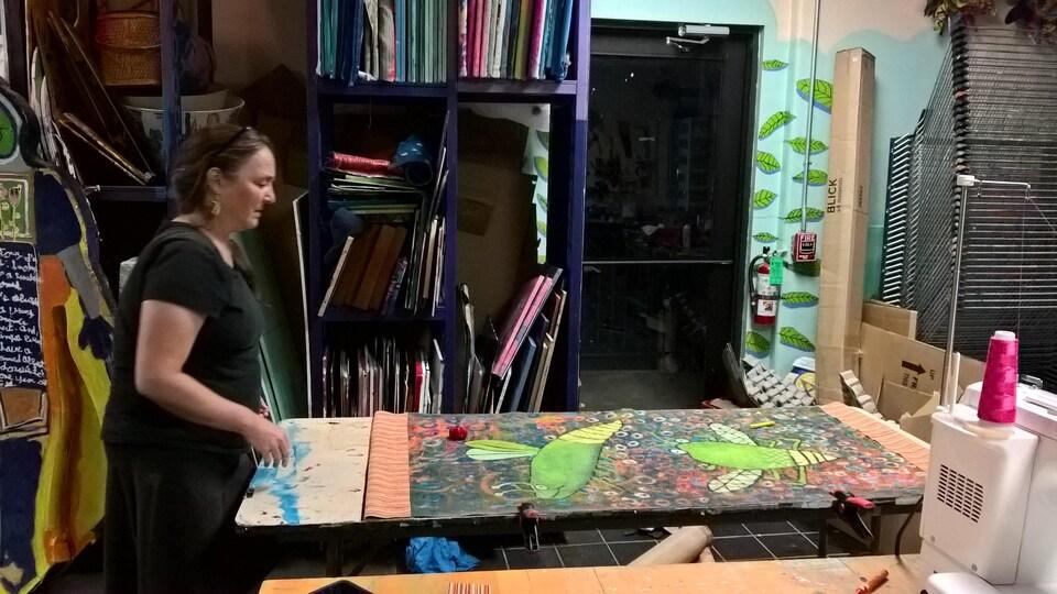 La fondatrice de Passion Works, Patty Mitchell, examine une banderole aux couleurs vives posée sur une table de son studio.